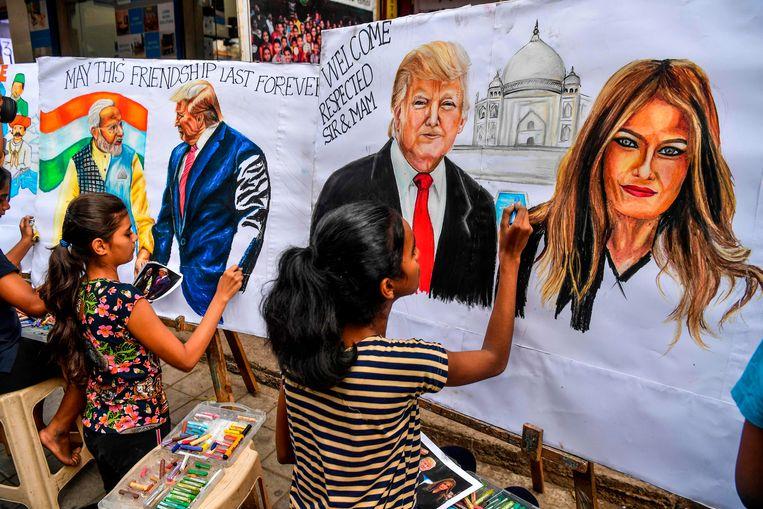 Kinderen maken afbeeldingen van Donald Trump en zijn vrouw Melania in afwachting van het bezoek aan de VS-delegatie.  Beeld AFP