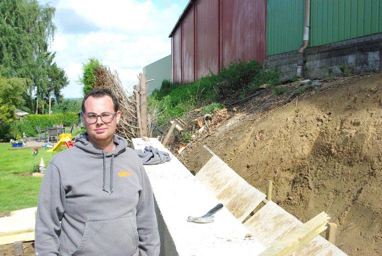 Aannemer Ruben Bollengier bij de talud waar achter hem nog asbest ligt.