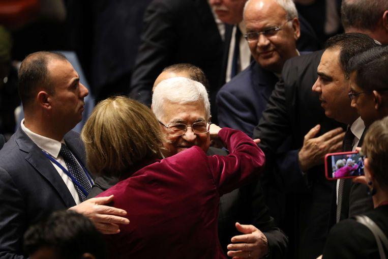 De Palestijnse president Mahmoud Abbas wordt begroet door diplomaten na een toespraak voor de VN-veiligheidsraad in New York dinsdag. Beeld AFP