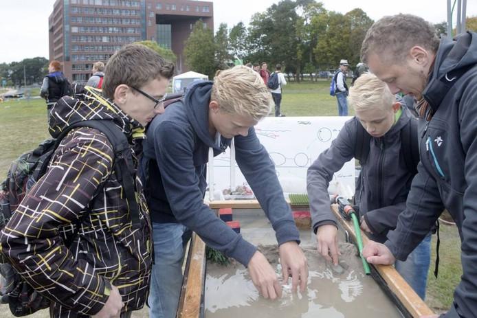 Deelnemers aan het Wereld Water College bouwen een dijk. Foto: Herman Stöver
