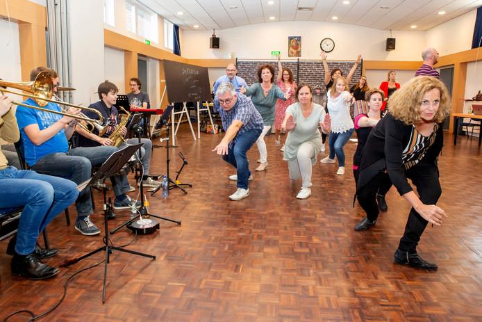 De leden van Invitéater tijdens een repetitie voor de musical DeKOORum, over een popkoor dat gaat repeteren in het koetshuis van een wereldberoemde zangeres die haar carrière voortijdig af moest breken.