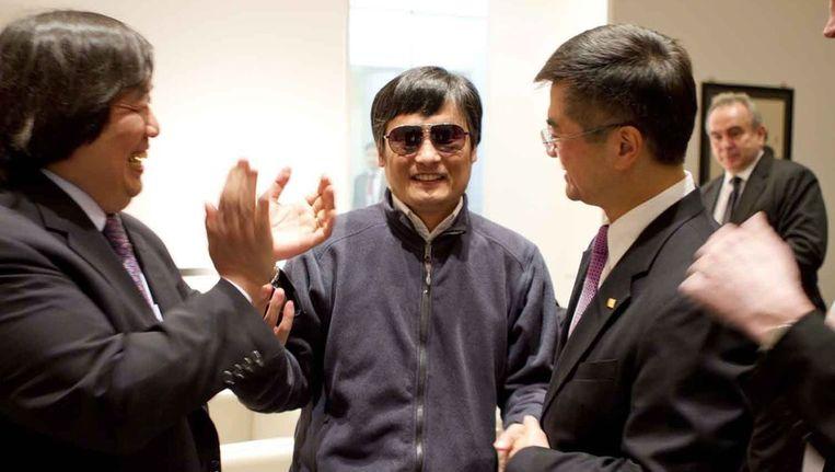 Chen (midden) schudt de hand van de Amerikaanse ambassadeur in China (rechts) Beeld epa