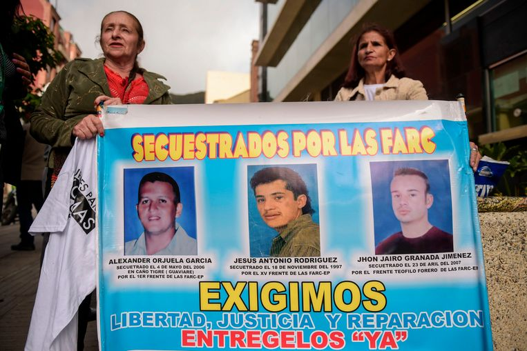 Vrouwen houden een spandoek omhoog met daarop de portretten van drie mannen die door FARC werden gontvoerd. Wij eisen vrijheid, gerechtigheid en compensatie', staat er onder de portretten geschreven.
