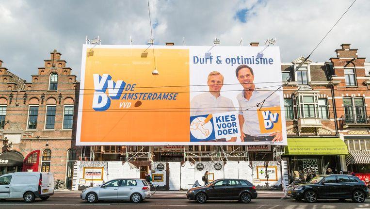 Mark Rutte en Eric van der Burg lachen Amsterdammers toe in de Van Baerlestraat. Beeld Tammy van Nerum
