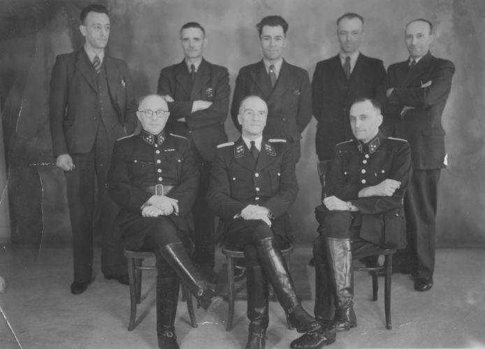 UTRECHT, 1942/1943  Vijf rechercheurs van de Centrale Controle, de afdeling van de Utrechtse politie die vanaf najaar 1942 belast is met het opsporen en arresteren van Joden, poseren op het hoofdbureau van de politie. Op de voorgrond de korpsleiding met in het midden hoofdcommissaris G.J. Kerlen. Deze fanatieke nazi werd op 3 september 1943 in het Willemsplantsoen, vlak bij zijn woning, geliquideerd door de verzetsvrouw Truus van Lier. Naast hem zijn medewerkers P.J.M. Thissen en G. van Grootheest. Staande links J. Smorenburg, de chef van de Jodenjagers van de Utrechtse politie. Hij heeft met zijn medewerkers honderden Joden opgepakt. Tijdens de oorlog viel hij in ongenade: hij werd betrapt op het verduisteren van waardevolle voorwerpen van zijn slachtoffers. Smorenburg werd daarop gearresteerd en tot een gevangenisstraf veroordeeld. Na de oorlog stond hij opnieuw voor de rechter, nu voor zijn aandeel in de Jodendeportaties. Hij werd uiteindelijk tot elf jaar veroordeeld, waarvan hij minder dan de helft hoefde uit te zitten.