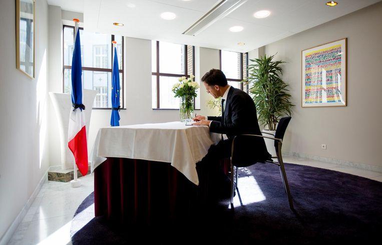 Premier Rutte tekent het condoleanceregister. Beeld anp