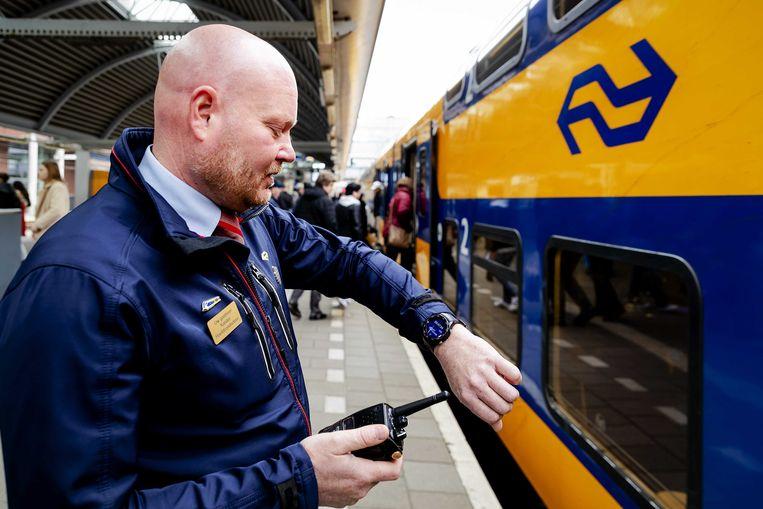 Een conducteur van de NS met een smartwatch. Het hulpmiddel waardoor een trein op de seconde nauwkeurig kan vertrekken en de samenwerking tussen collegae verbetert.  Beeld ANP, Robin van Lonkhuijsen