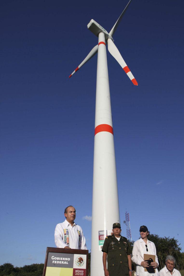De mexicaanse president Felipe Calderon start met een druk op de knop de windturbine die de klimaatconferentie in Mexico van energie gaat voorzien. Beeld ap