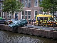 Auto bungelt boven het water, inzittenden houden het droog