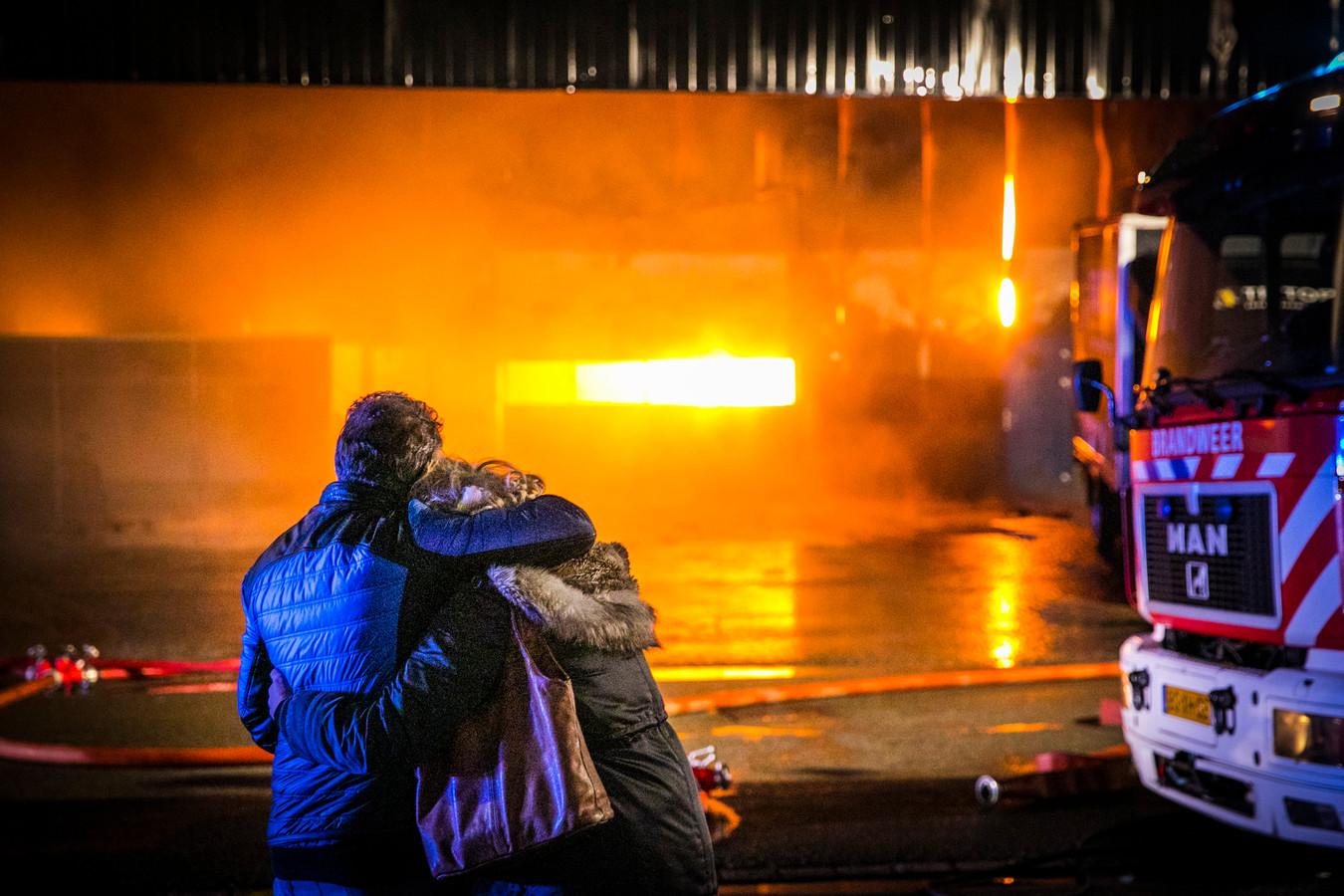 Medewerkers van het bedrijf kijken verslagen naar de vuurzee.