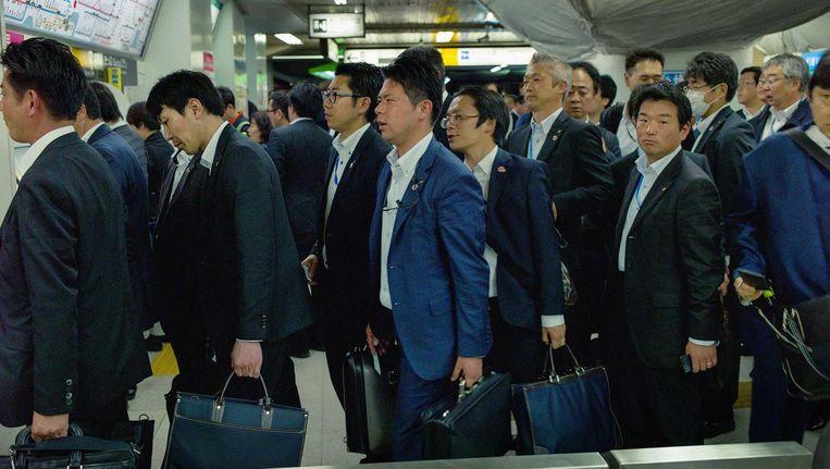 Japanse zakenlieden in de rij op het Shinbashi Station in Tokio. Beeld Kentaro Takahashi