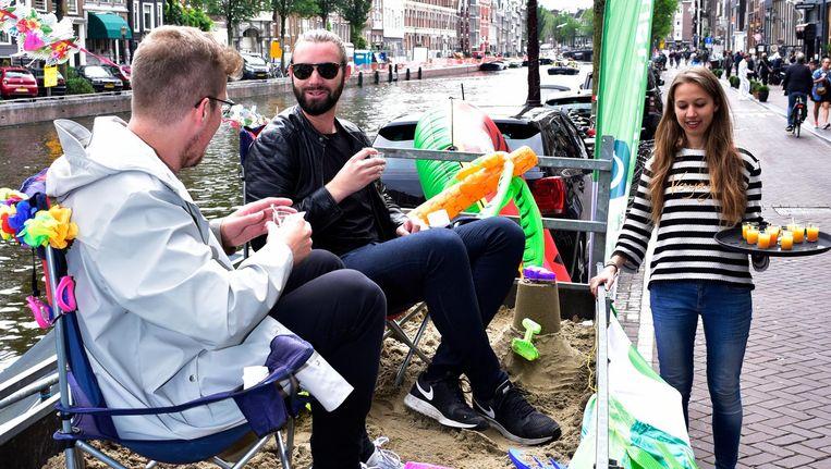 Parkeerkplekken zouden Amsterdammers meer op kunnen leveren, vindt Milieudefensie. Een stadsstrand bijvoorbeeld. Beeld Milieudefensie / Gerda Hornema