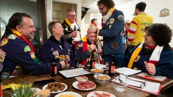 De huiskamer van de Kletsavonden boven café De Smidse, jury en allerlei mensen die er ook niet hoeven te zijn. De jury aan tafel met links staande aanelkaarkletser Leo van Gerven.