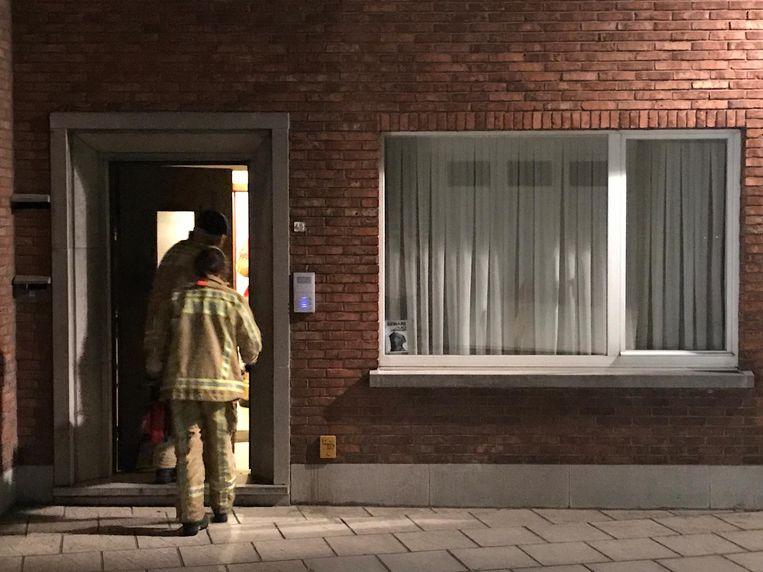 De brandweer stapt de woning binnen om de ingestampte deuren te beveiligen.