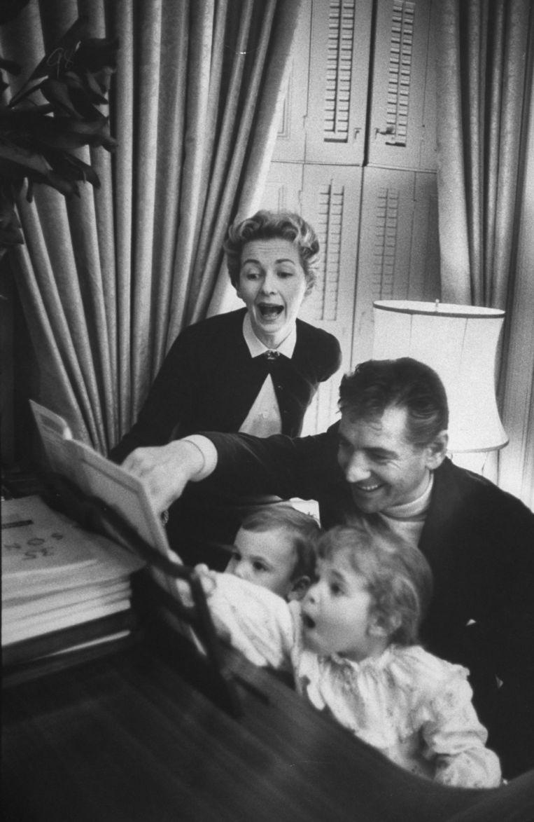 Leonard Bernstein met Felicia Montealegre en hun kinderen Alexander (l.) en Jamie (r.) thuis achter de piano, in 1956. Beeld Getty