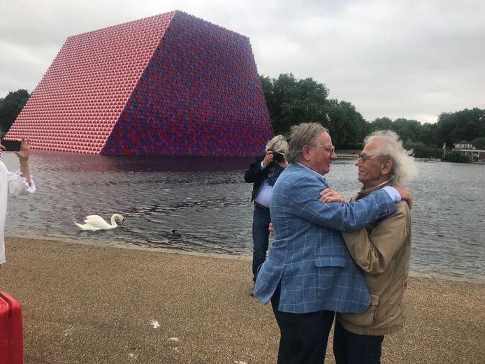 Bij het kunstwerk in Londen, gemaakt van vaten van Janus Vaten uit Oosterhout. 'Frits!', zegt de kunstenaar (rechts) enthousiast als hij Janus senior ziet. De twee pakken elkaar stevig vast. Zoon Ton lachend: 'Elke keer herkent hij mijn vader weer'.
