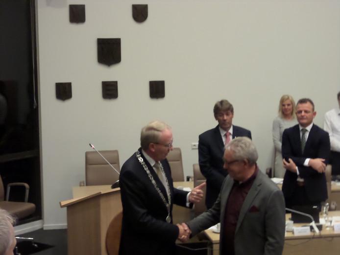 Burgemeester Noordergraaf feliciteert Henk van Putten, de wethouders kijken toe.