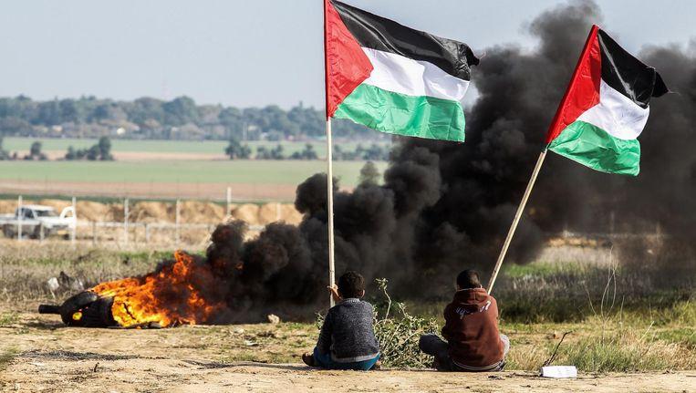 Palestijnse demonstranten zwaaien met hun nationale vlag. Ze protesteren tegen het achterhouden van de Amerikaanse subsidie voor de UNRWA. Beeld anp