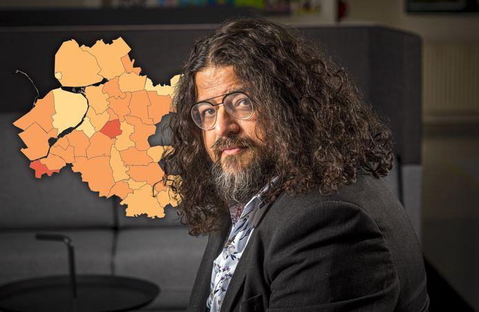 GGD-arts Ashis Brahma, met op de achtergrond de meest recente corona-cijfers in kaart.
