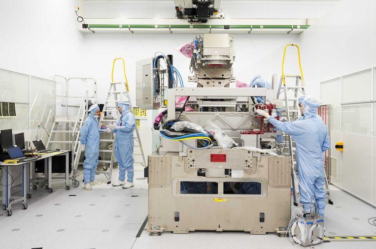 Werknemers van ASML in de stofvrije ruimte, de zogenaamde cleanroom, waar chips worden gemaakt. ASML maakt machines voor de halfgeleiderindustrie die in het buitenland goed worden verkocht. Beeld ANP