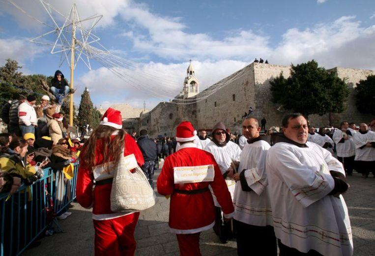 Twee kerstmannen vragen aandacht voor de situatie op de Gazastrook. Op de achtergrond de kerk waarvan wordt aangenomen dat Jezus daar is geboren. Foto EPA/Jim Hollander Beeld