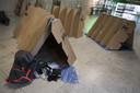 In een gevangenis worden de kartonnen tentjes gebouwd.