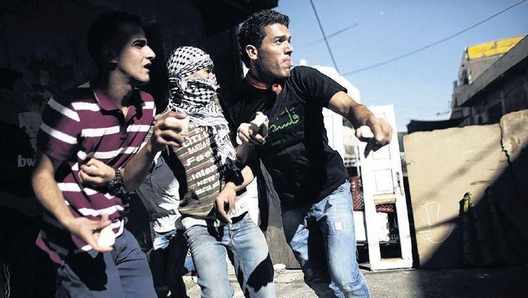 Hebron, 23 september: Palestijnse jongeren op de Westoever gooien stenen naar Israëlische militairen. Beeld afp
