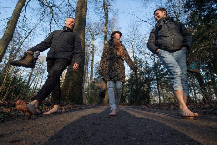Annelies van den Bogert uit Meteren wandelt op blote voeten met haar broer Gijsbert (links) en Marinus Behrens door het parkbos in Neerijnen