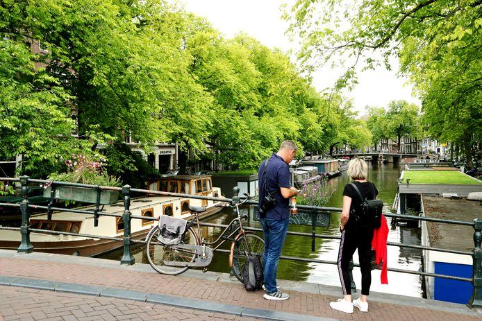 Toeristen op een brug over de Brouwersgracht met enkele woonboten die aan toeristen worden verhuurd. Zomer in Nederland, Jordaan