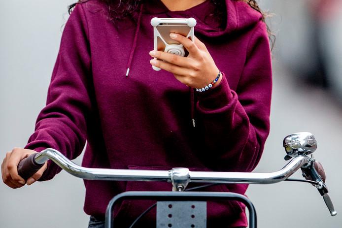 Een tiener appt op de fiets, straks kan zij een fikse boete krijgen.