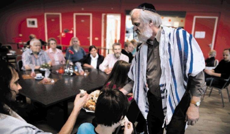 Voorganger Gerard Wijtsma, met baard, keppeltje en gebedsmantel, deelt brood uit. (Trouw) Beeld