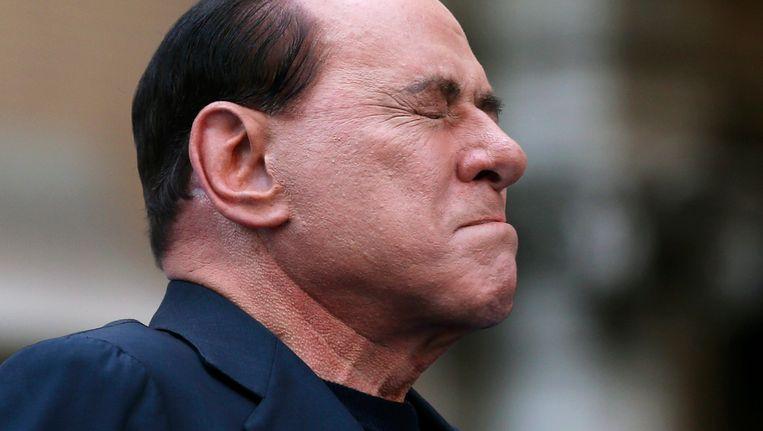 Silvio Berlusconi reageert op demonstranten bij het binnengaan van de rechtbank begin augustus, waar een zaak tegen hem diende vanwege belastingfraude. Beeld Reuters