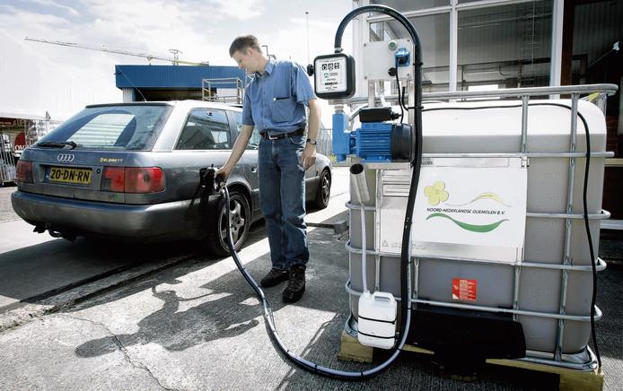 Een automobilist gooit zijn auto vol met biobrandstof uit koolzaad (archief)