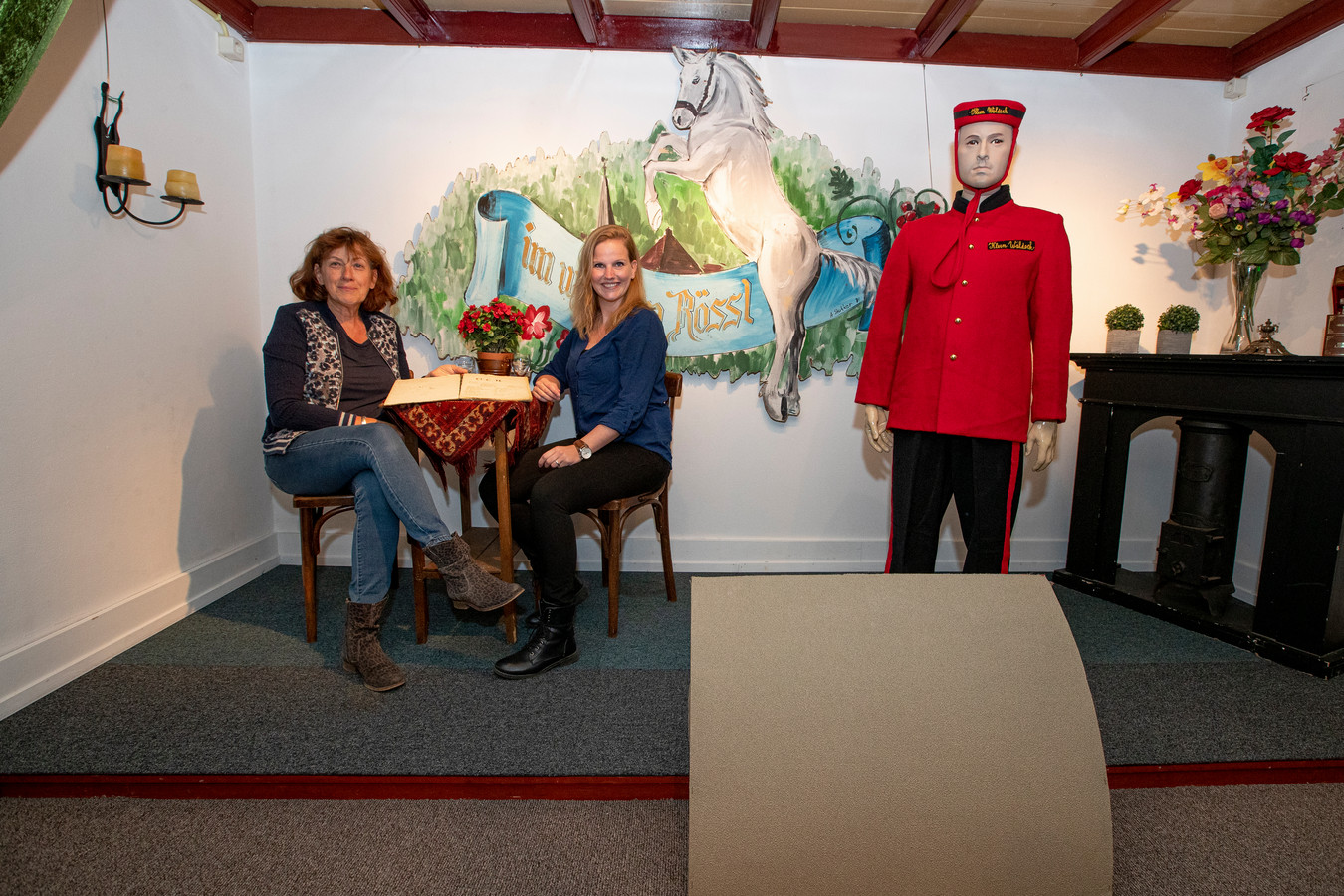 In de oudheidkamer herleeft de 75-jarige historie van Toneelvereniging Ontspanningsclub Holten. Ria Kappert (l) en Susan Bronsvoort bladeren in de archieven terwijl een acteur poseert.