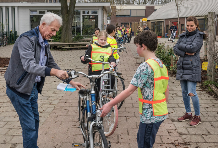 Henk Baron inspecteert de fiets van een leerling van basisschool Op Weg.