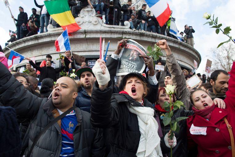 De Place de la République zondagmiddag (links). Rechtsonder omhelst de Franse president François Hollande Beeld Ton Koene