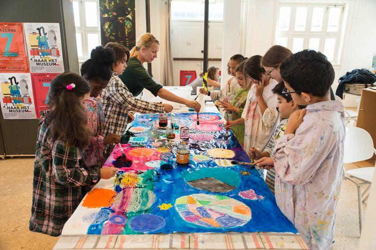 Kinderen schilderen en maken logo's bij zomerschool Noordje in een Ruimte-thema. Beeld Charlotte Odijk
