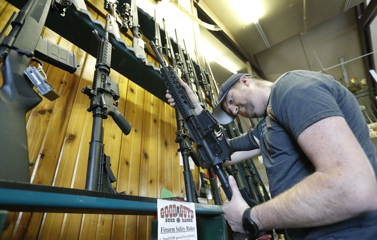 Een man bekijkt een AR-15 aanvalsgeweer dat te koop staat in een wapenzaak in Utah. Datzelfde type geweer werd gebruikt door de 19-jarige schutter die op 15 februari een bloedbad aanrichtte op een middelbare school in Florida. Beeld Getty Images