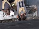 Brandweermannen halen de egel uit de afvoer in de ombouw rond het gebouw.