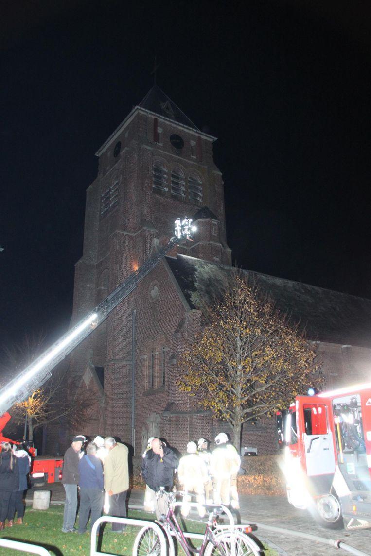 De brandweer aan de slag bij de schoorsteen van de zijbeuk.