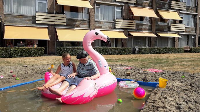 Vossenberg-bewoner Harry van Boxtel (86) zit gezellig samen met de 9-jarige Lena op de grote roze opblaasflamingo op het water.