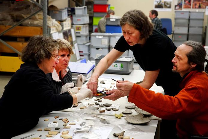 Vrijwilligers selecteren resten van oude vondsten in het depot.