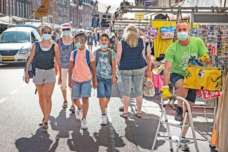 De meeste bezoekers en marktkooplui hebben een mondkapje op, desnoods een van de gratis blauwe kapjes die twee lopende uithangborden uitdelen.  Beeld Guus Dubbelman / de Volkskrant