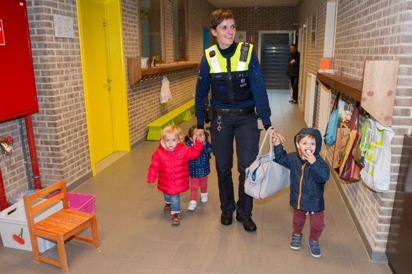 Een agente brengt enkele kindjes naar buiten. Haar eigen zoontje (rechts) verblijft ook in de crèche en moest dus ook naar de basisschool gebracht worden.