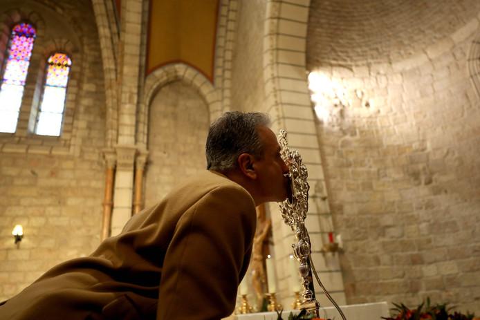 Een gelovige drukt een kus op het relikwie.