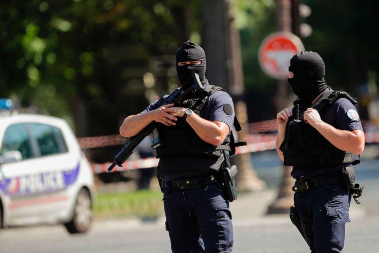 Zwaarbewapende politieagenten patrouilleren op de Champs-Elysees na de aanrijding. Beeld AFP PHOTO / Thomas SAMSON