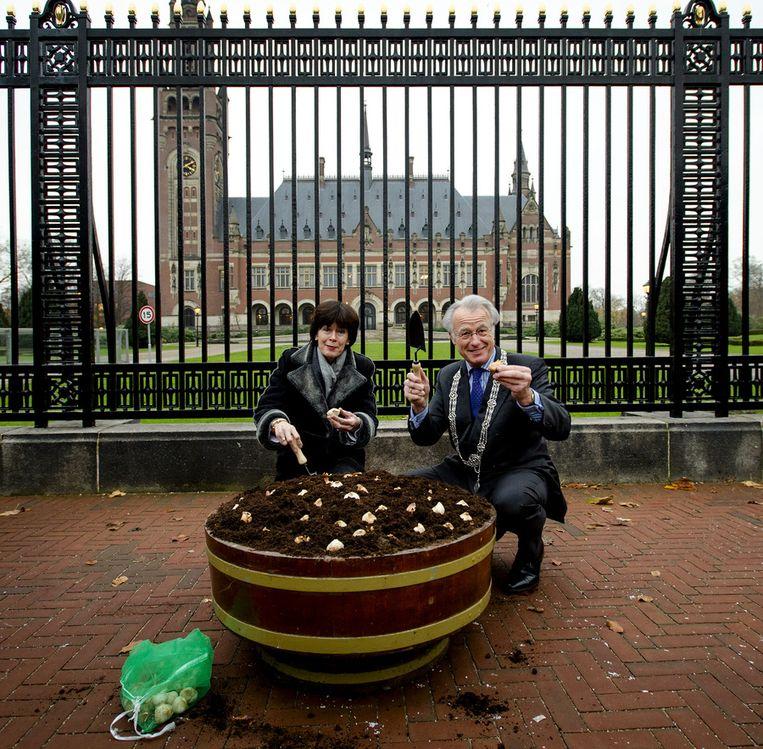 Burgemeester Jozias van Aartsen en secretaris-generaal van het ministerie van Buitenlandse Zaken Renee Jones-Bos planten tulpenbollen voor het Vredespaleis. Voor de grootste top die ooit in Nederland wordt gehouden, de Nuclear Security Summit in maart 2014, is een speciale tulp gekweekt Beeld anp