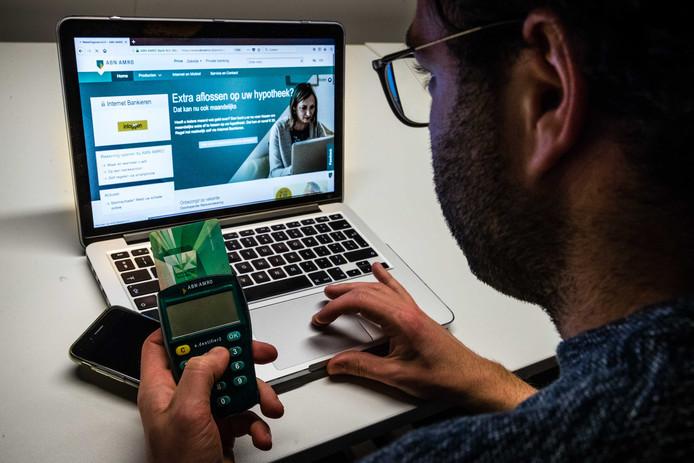 Een man aan het Internet Bankieren met ABN Amro. Het telebankieren van de bank kampte dit weekend met een storing door een DDoS-aanval