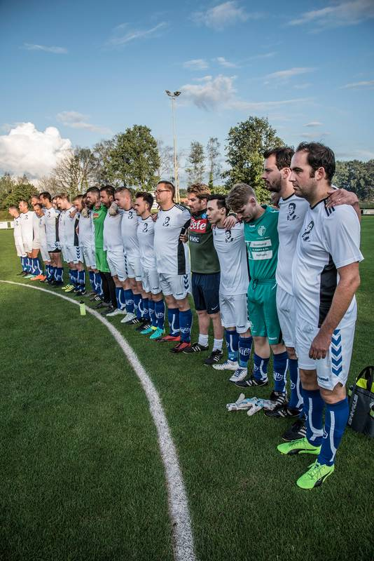 Een minuut stilte voor aanvang van de benefietwedstrijd in Holthees. Het derde team van de club draagt shirts met de beeltenis van Ivo van Tongeren.