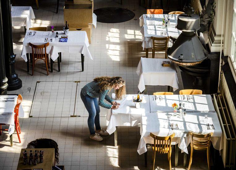 Een medewerker van een restaurant bereidt zich voor op de heropening van de horeca tijdens het coronavirus.  Beeld ANP